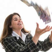 Hispanic woman throwing money to the air. Happy lady enjoying a cash prize. Cheerful lady enjoying her having money. Celebrating a successful business